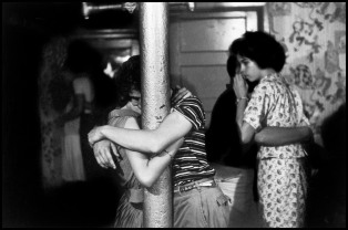 USA. Brooklyn, NY. 1957. Couple necking on pole at basement party while girl looks on, from Brooklyn Gang.