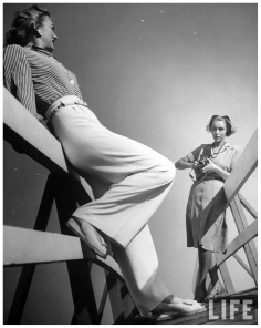 photographer-nina-leen-lining-up-shot-of-fashion-model-who-is-wearing-slacks-posing-casually-in-fore-1954